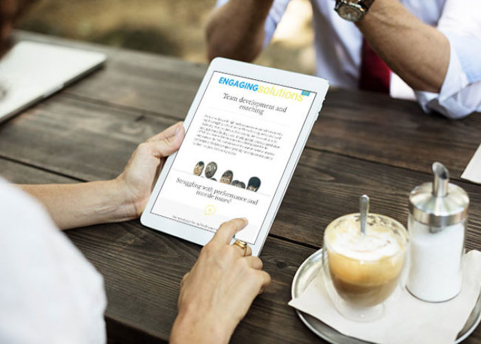 A man sitting at a wooden outdoor table with a tablet showing the Engaging Solutions website